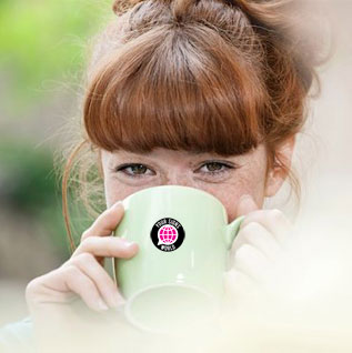 A woman drinks from a mug featuring YSW logo