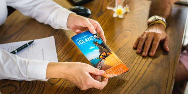 Travel brochure is handed to a client