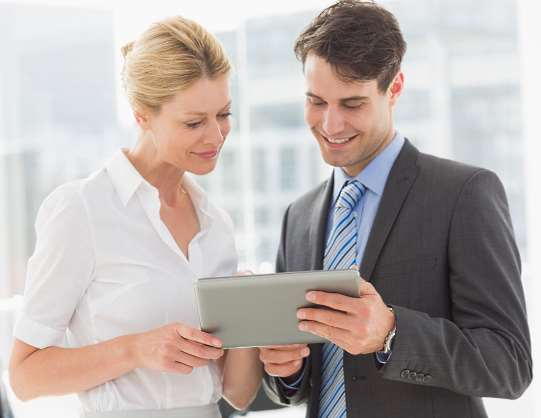 A designer and a client review a design in a tablet