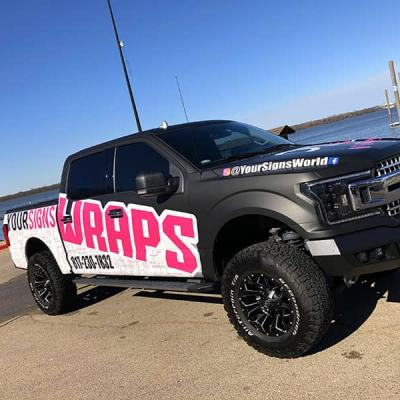 Vinyl-wrapped pickup truck displaying YourSignsWorld's vehicle wrapping service info