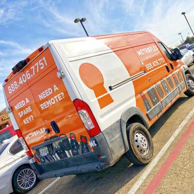 Rear view of a locksmith vinyl-wrapped van. Orange and white design.
