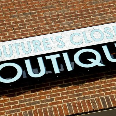 Front lit channel letters sign on a brick wall for Couture's Closet Boutique